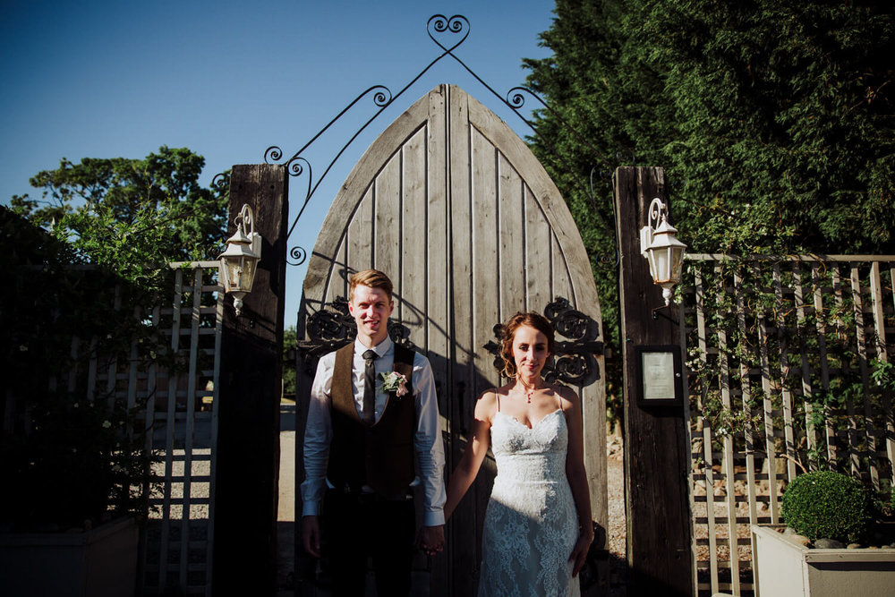 bride and groom holding hands in front of gate
