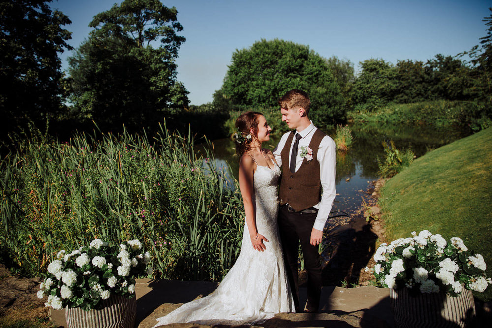 wide angle lens photograph of bride and groom in front of lake at alcumlow farm
