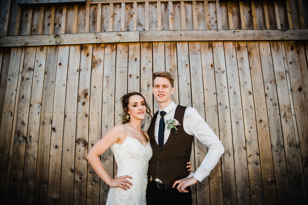 newlyweds portrait in front of wooden barn doors