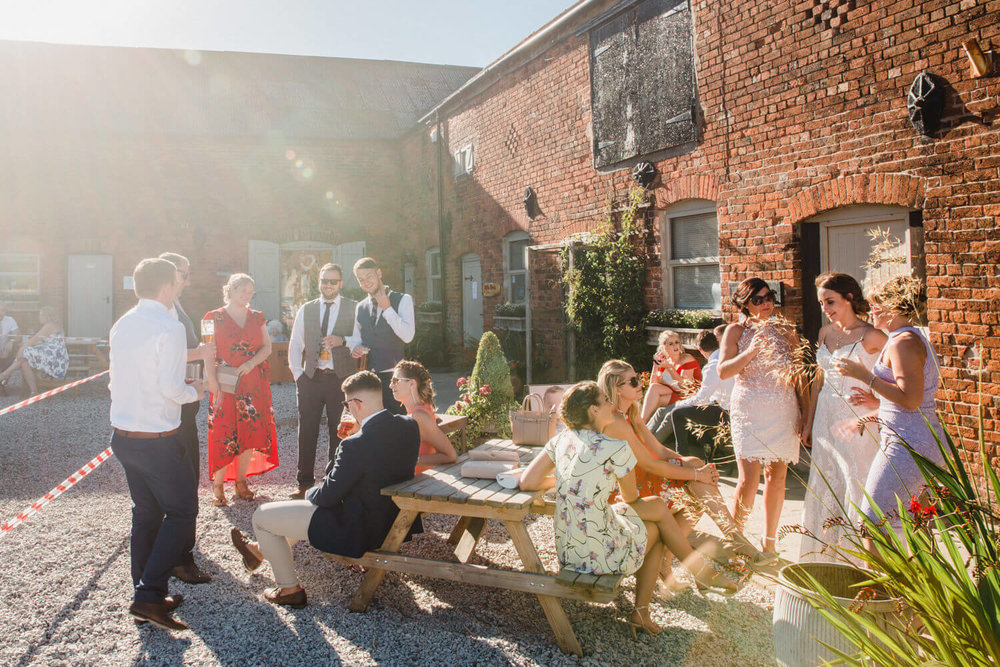 outdoor sun shining down on guests in courtyard at alcumlow hall farm