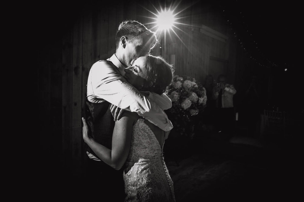 close up black and white photograph of bride and groom holding each other