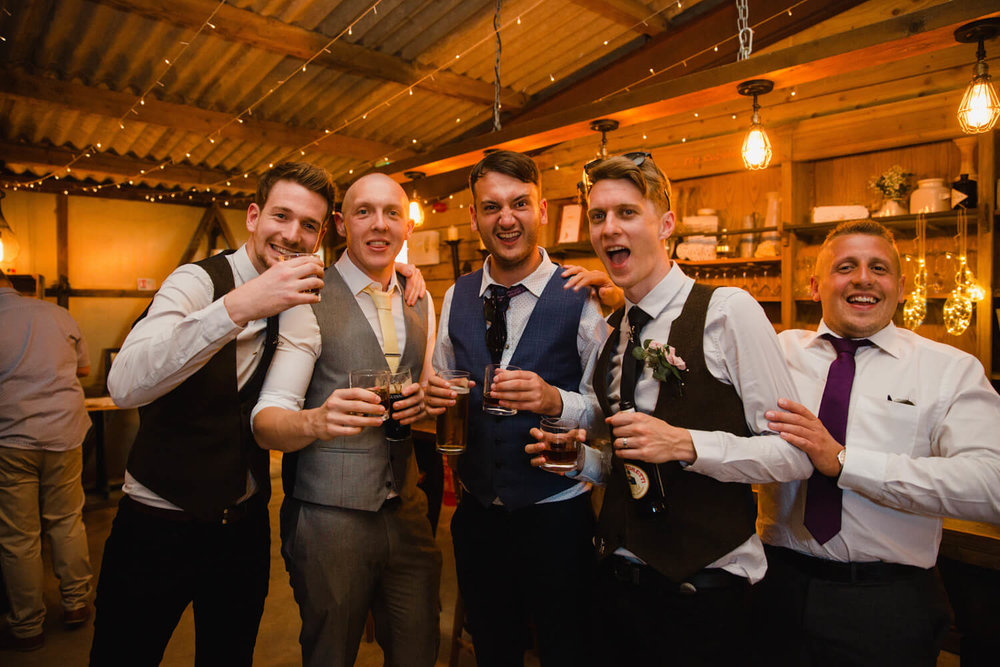 groom and friends posing to camera at bar