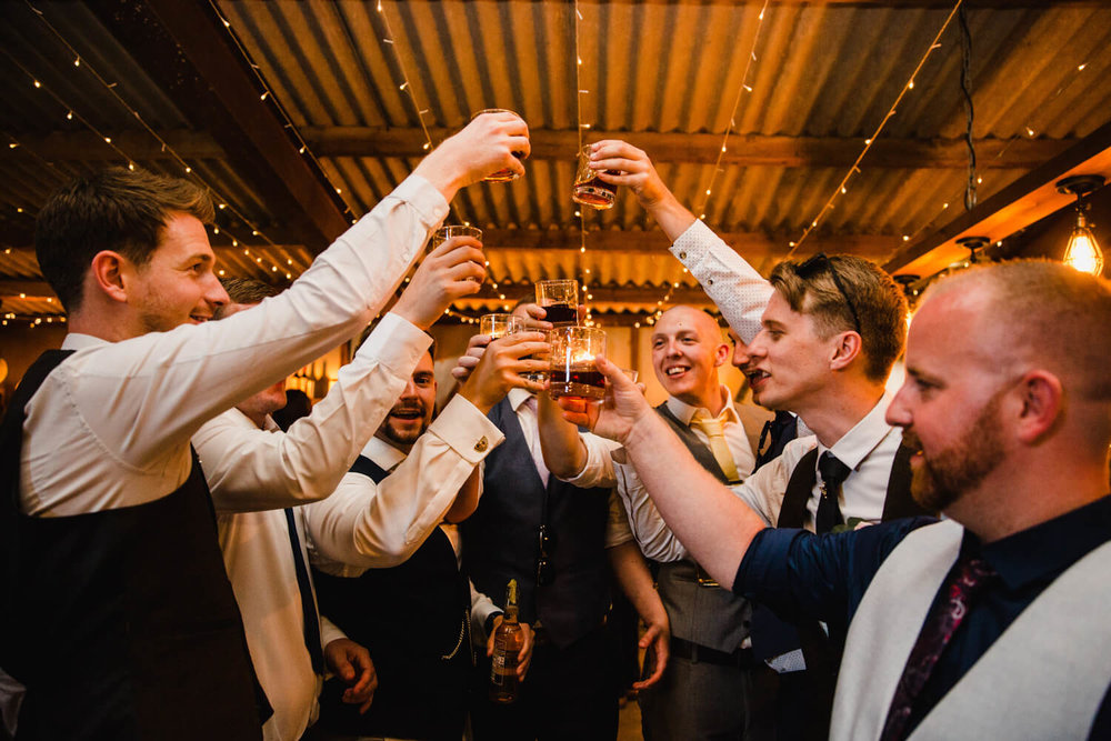 groom and friends raise glasses in celebration