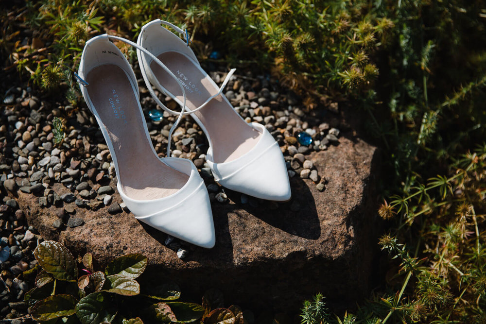 white wedding shoes on stone in garden