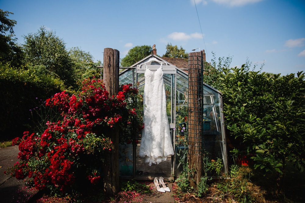 Wedding dress hanging from greenhouse