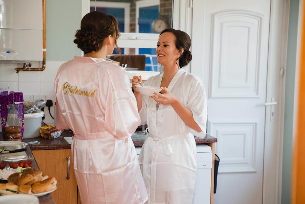 bride with bridesmaid in kitchen of house