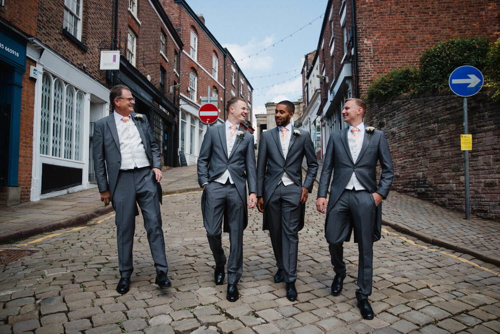 groom walking with groomsmen on cobbled street to ceremony