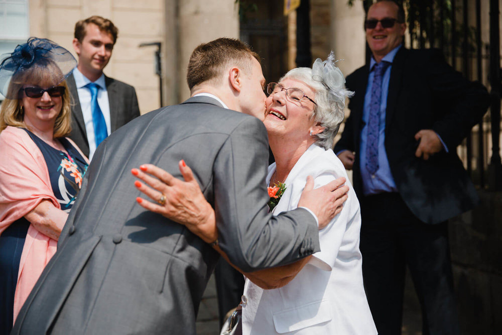 groom greeting and hugging grandma at church