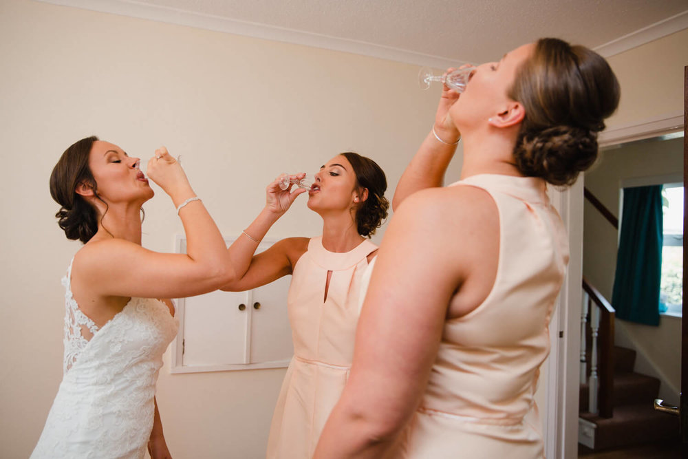 bride with bridesmaids having shots of alcohol