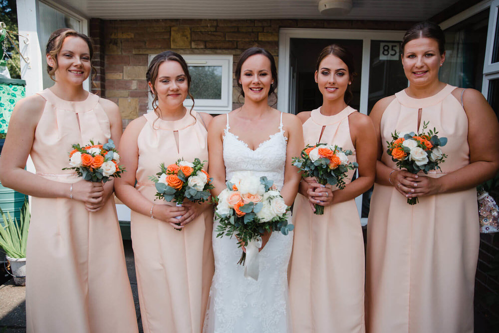 bride with bridal party at home holding bouquets