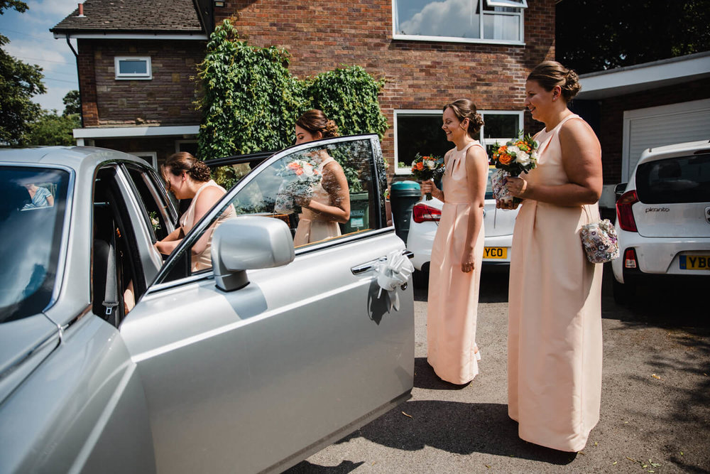 bridesmaids entering wedding car
