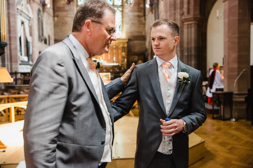 groom talking to father at top of aisle