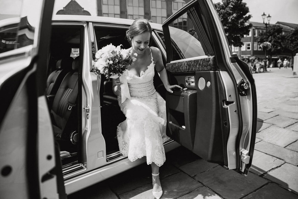 black and white photograph of bride stepping out of wedding car