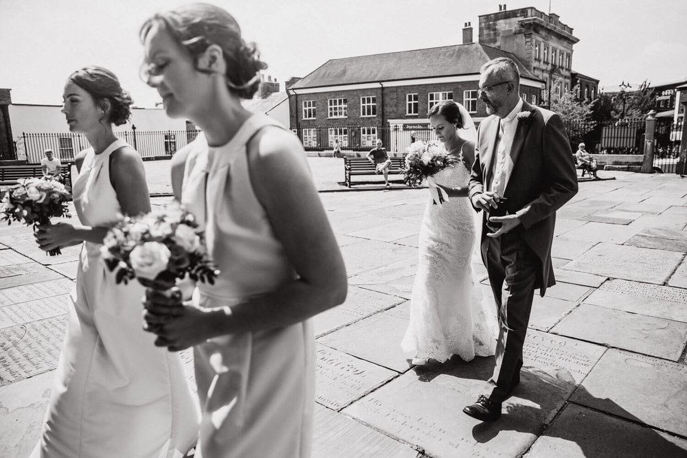 black and white photograph of bride walking to ceremony with father