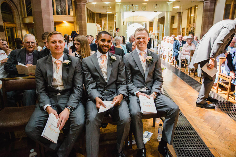 groom sat at front of church with groomsmen