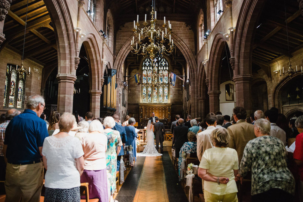 wide angle lens photograph of bride and groom at top of aisle of church exchanging vows