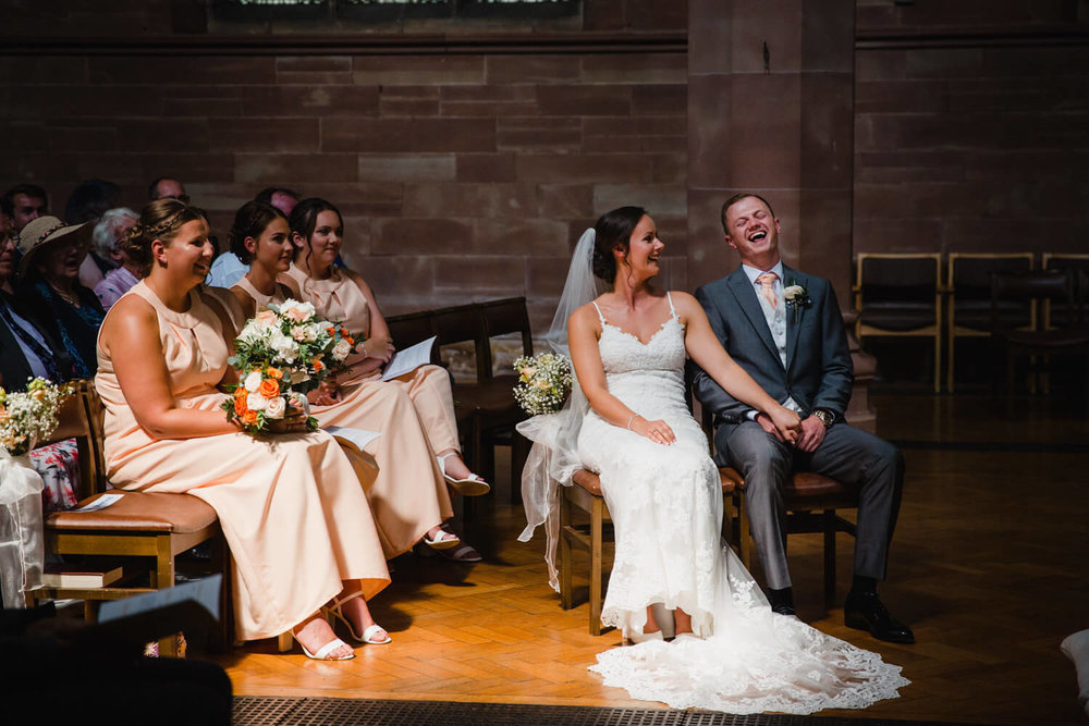 groom laughing at joke told by vicar in church
