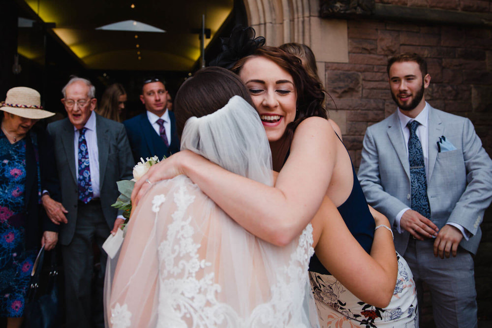 wedding guest hugs and congratulates bride