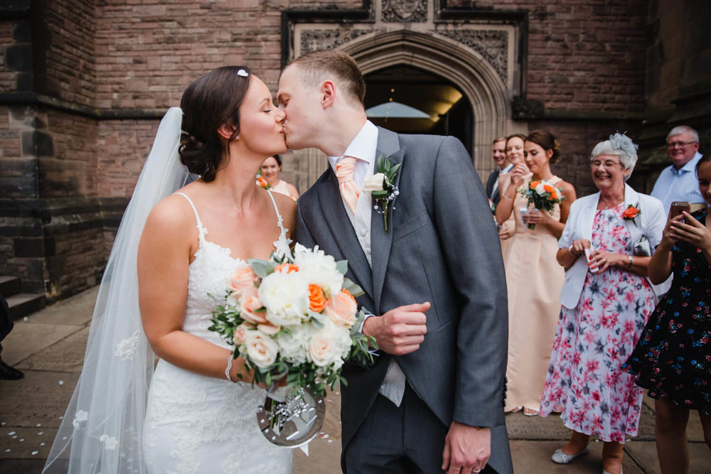 newlyweds share kiss with wedding party looking on