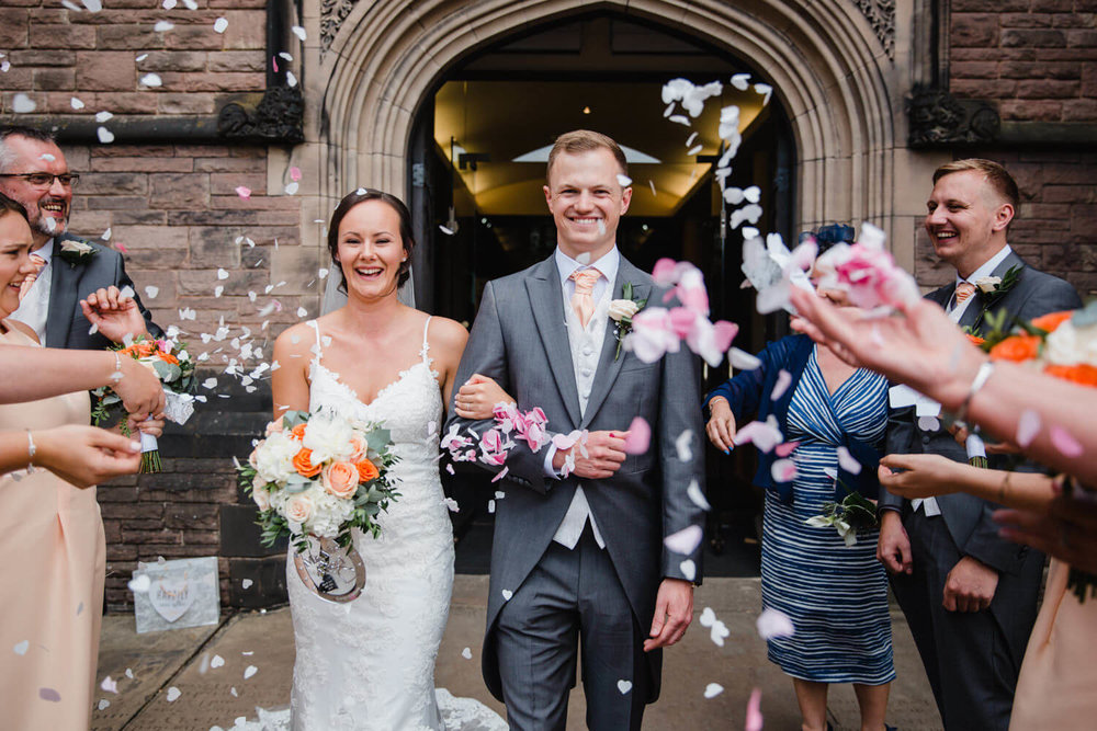 bride and groom walk through confetti thrown by friends and family
