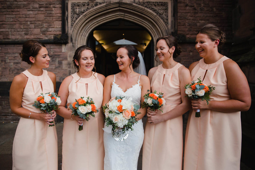 bride and bridesmaids pose for portrait holding bouquets outside church