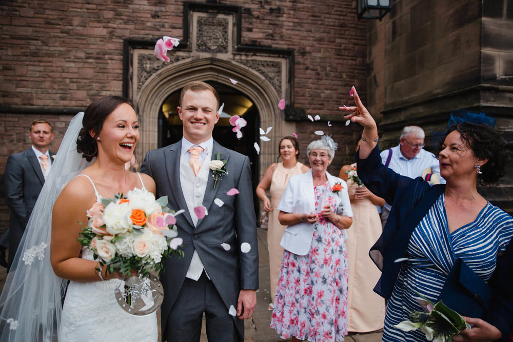 mother of bride throws confetti over newly wedded couple
