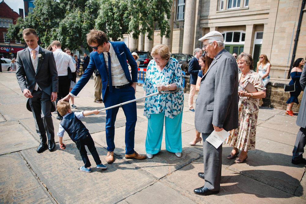 page boy pulling grandmas crutch outside church