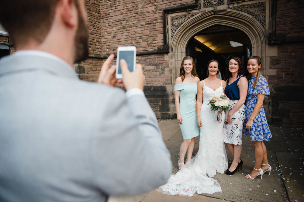 bride and friends pose for camera phone photograph