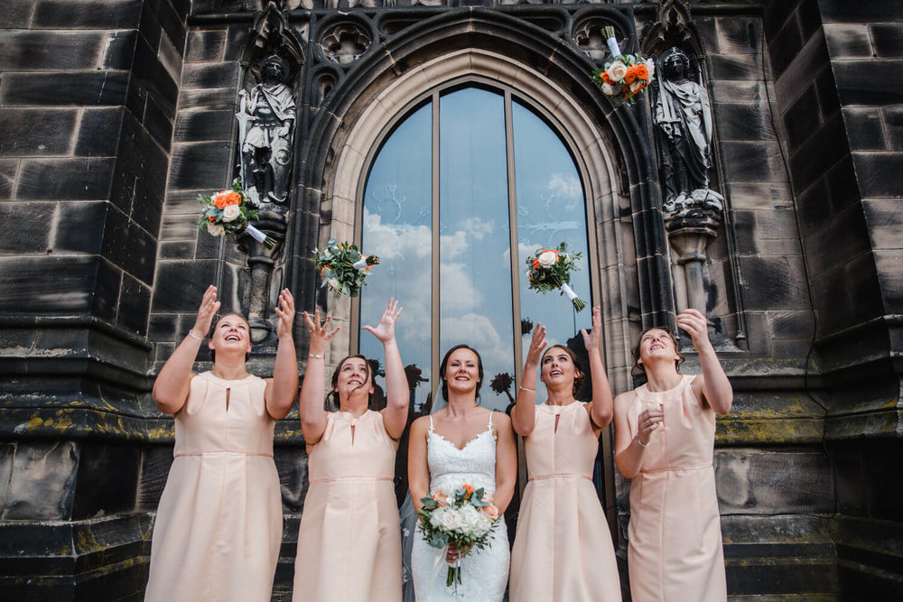 bride and bridesmaids throw bouquets up in the air