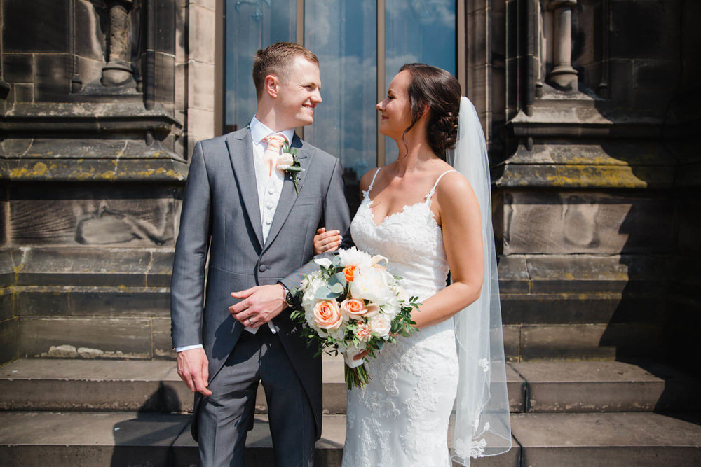 bride and groom pose for portrait outside church