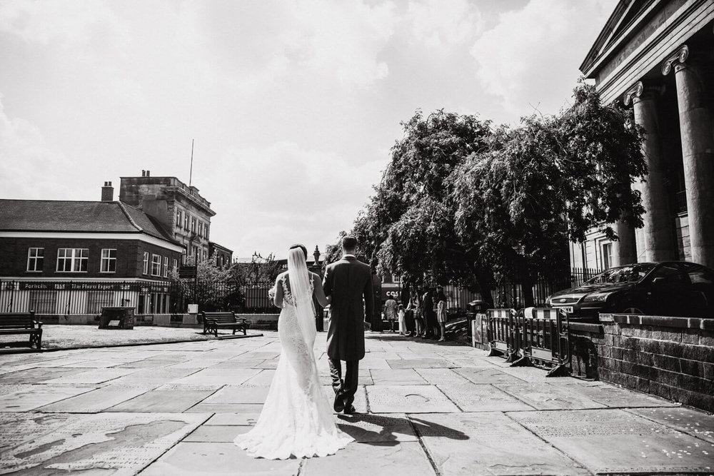 black and white photograph of newlyweds walking to car