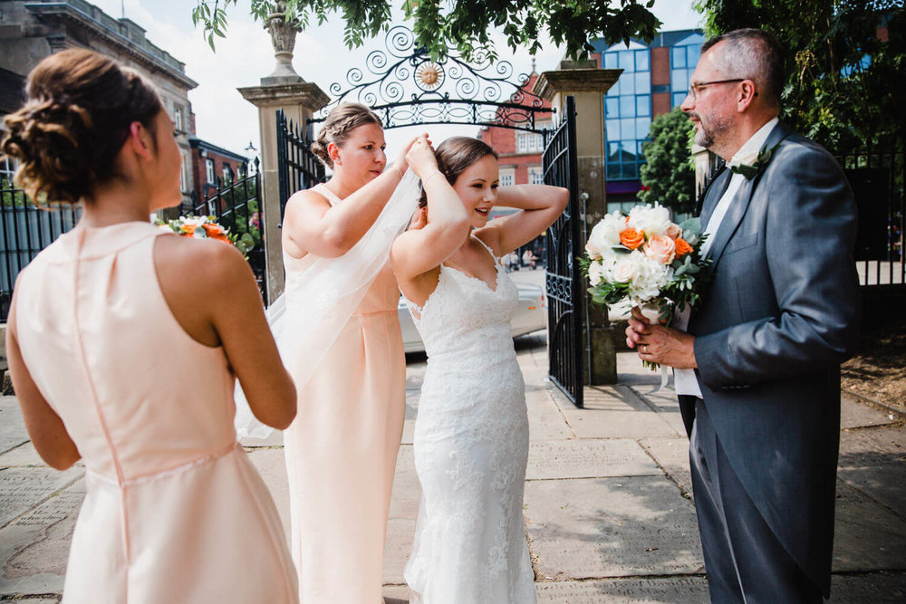 bridesmaids help bride attach wedding dress veil
