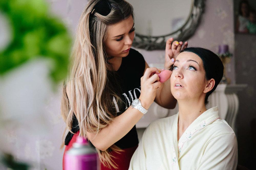 bride having eye liner applied before ceremony