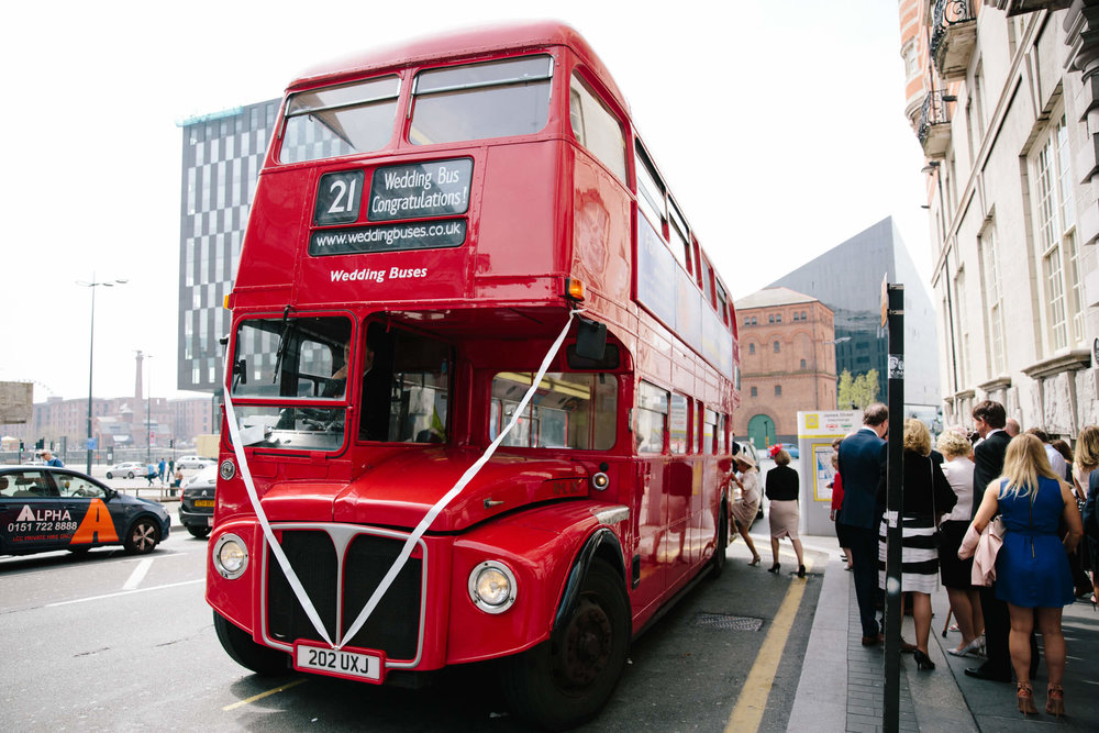 Red double decker wedding bus outside wedding venue for guests