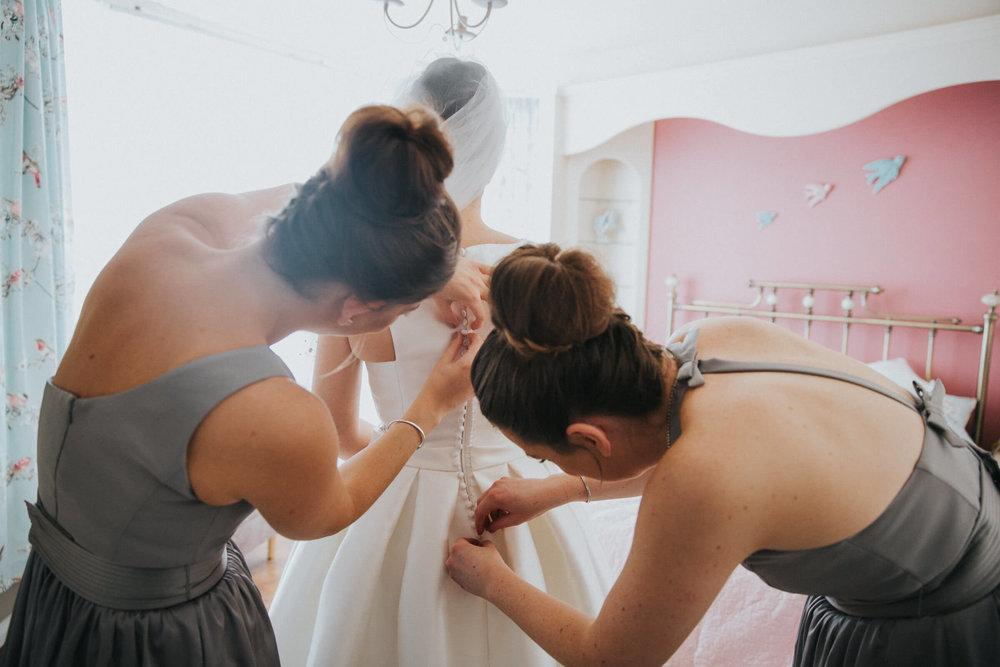 bridesmaids fastening bride wedding dress before ceremony