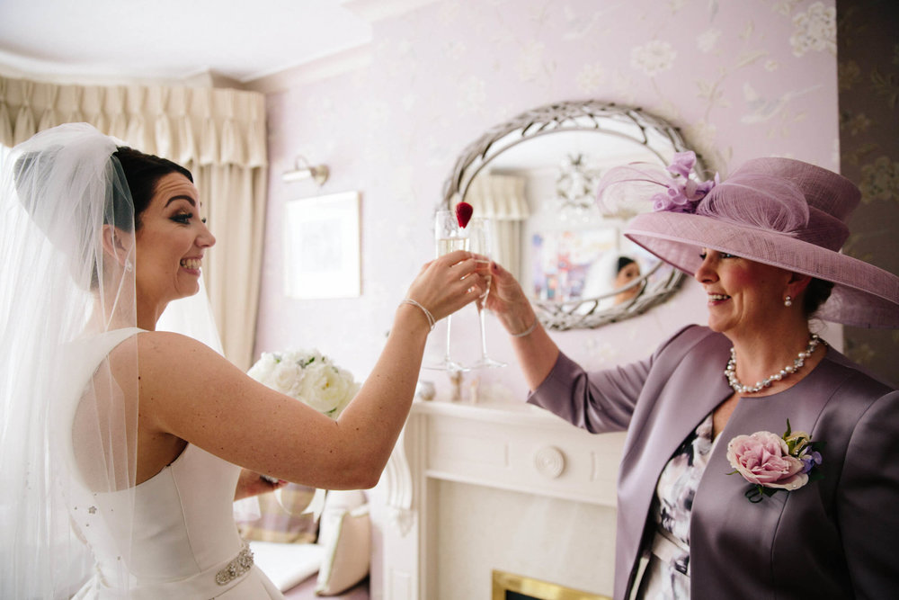 bride sharing champagne flute with mother