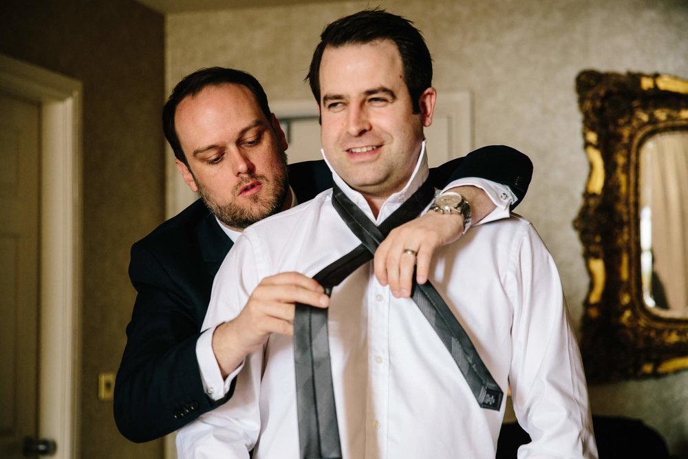 best man fastening tie of groom