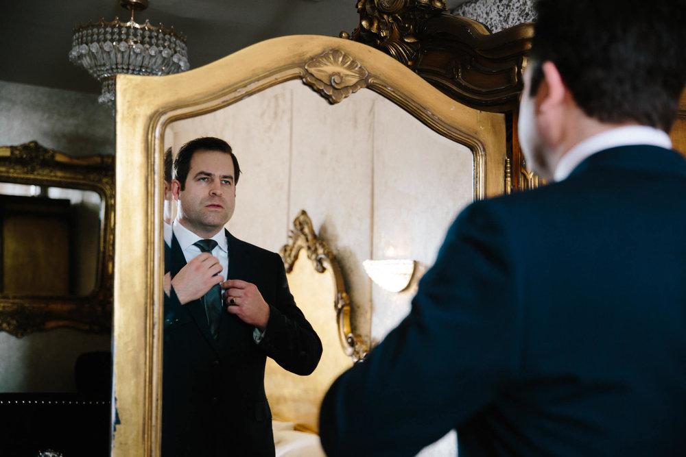 groom straightening tie in mirror at 30 James Street