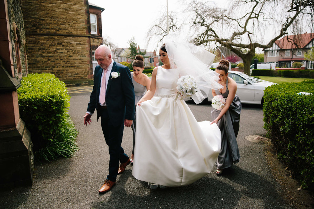 bride walking into church with father and bridesmaids for ceremony