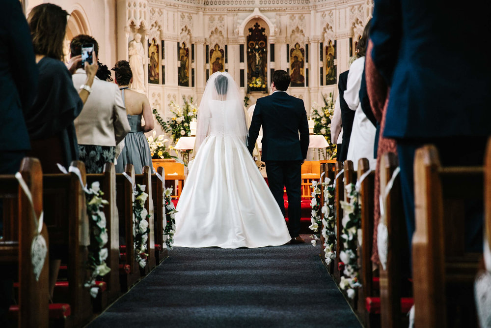 photograph taken from back of church of bride and groom holding hands