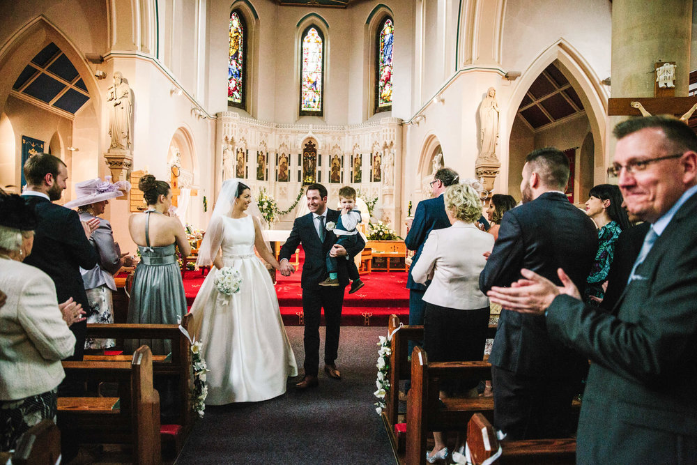 newlyweds hold hands while congratulated by friends and family