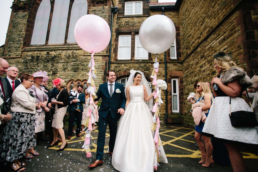 newly wedded couple hold celebratory balloons