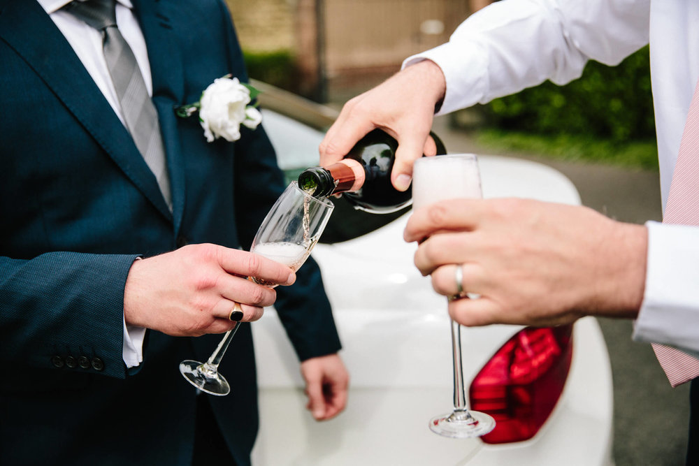 wedding car chauffeur pouring champagne for newly married couple