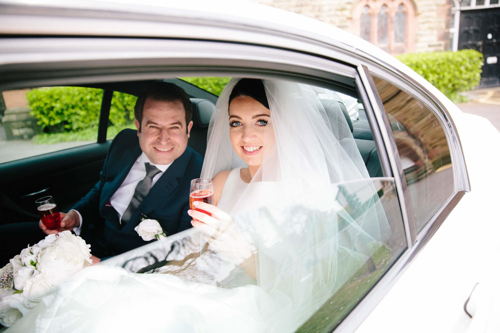newlyweds sat in wedding car looking into camera for pose