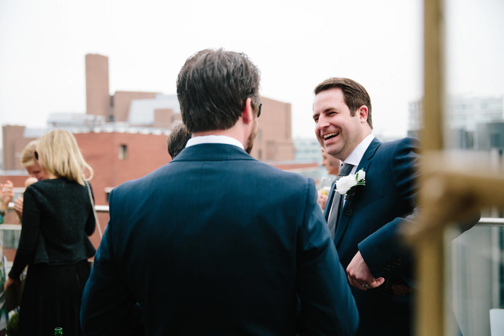 groom sharing jokes with guests on balcony