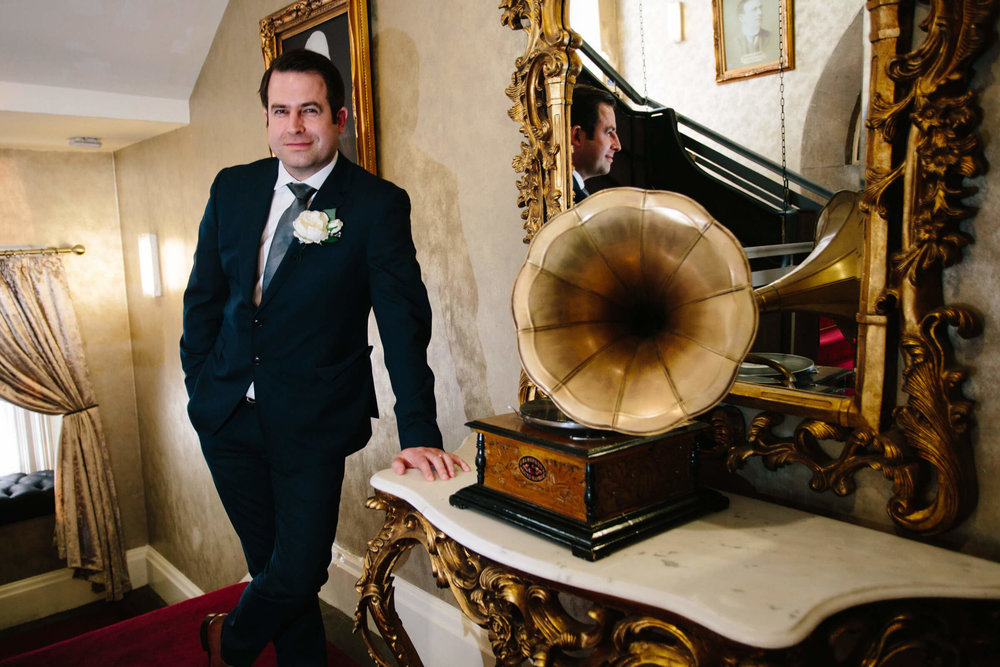 Groom poses with jukebox in lobby of hotel
