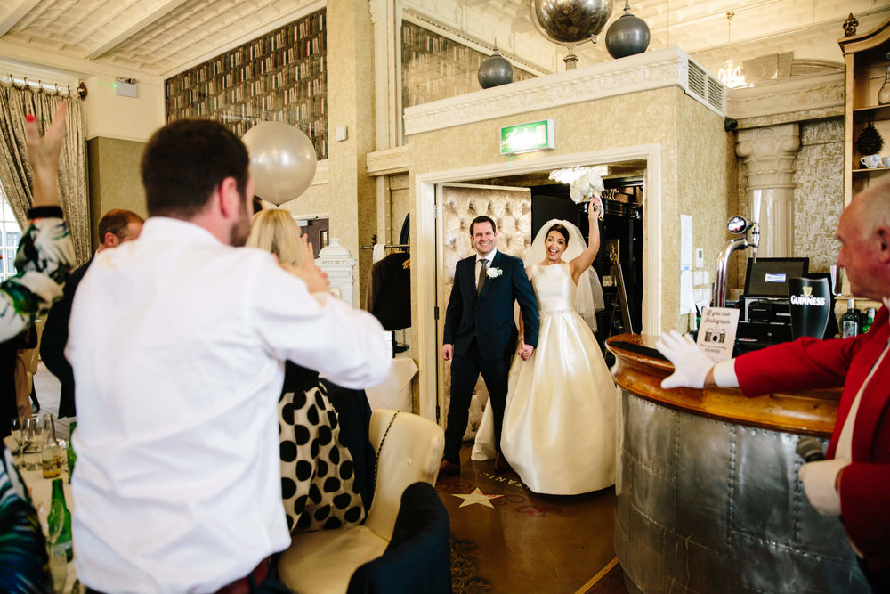 bride and groom enter wedding breakfast room and congratulated by guests