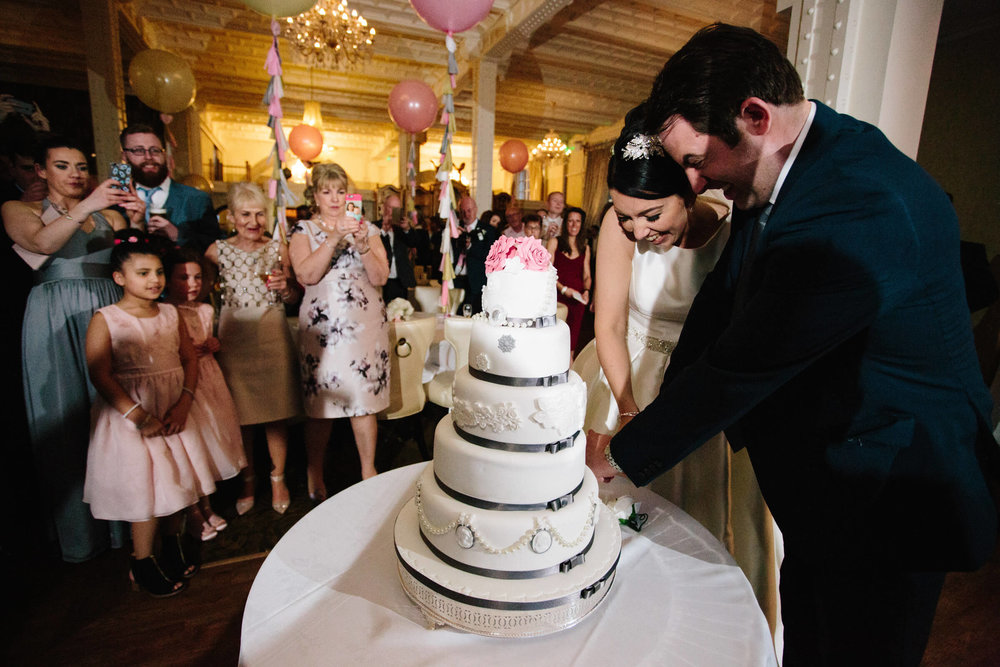 Newlyweds cut cake with family taking photographs with camera phones