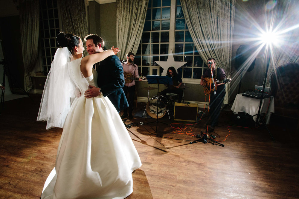 bride and groom holding each other while band play music