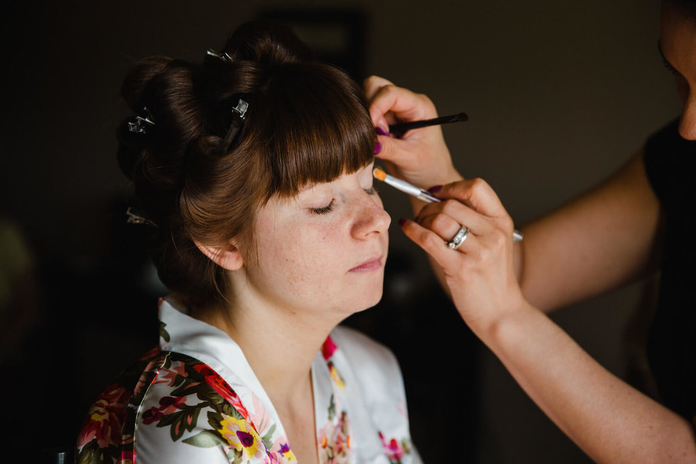 close up photograph of bride having make up applied
